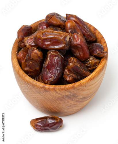 dried dates in wooden bowl isolated on white