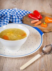 Noodle soup with carrots and vegetables in white bowl