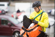 Young Male Cyclist Putting Package In Courier Bag