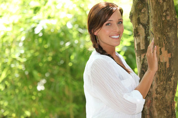 Summery woman standing against a tree