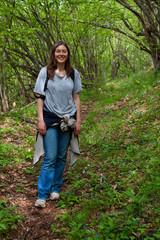 Giovane donna sorridente nel bosco