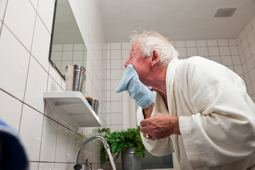 Senior man washing his face after shaving.