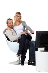 woman sitting on her boyfriend and watching television