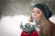 .Young woman with  cap blowing snow, winter fun