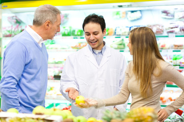 Customers talking with a shop assistant at the supermarket