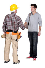 A construction worker and his trainee shaking hands.