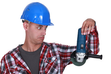 Uneasy tradesman looking at an angle grinder