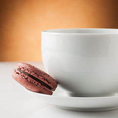 Cup of coffee with a chocolate macaron