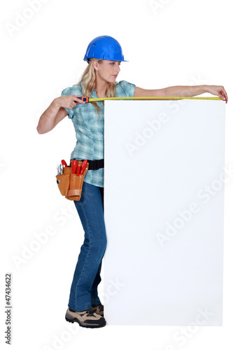 Construction worker measuring a blank board