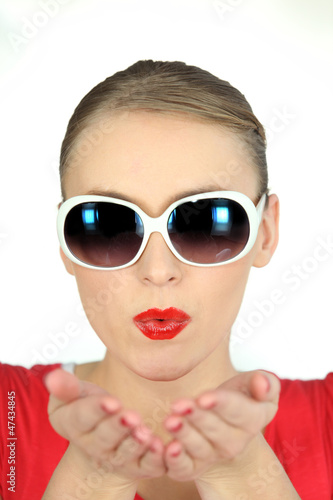 Woman with glasses pulling air kiss