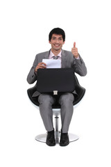 seated young businessman with thumb up