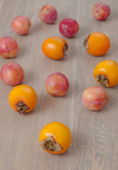 Persimmon fruit and pink plums