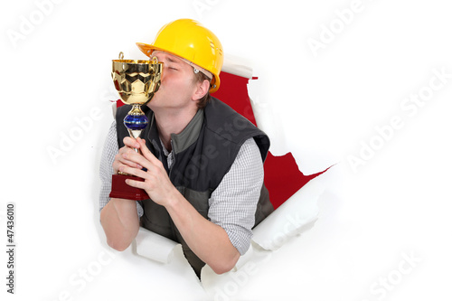 Construction worker kissing a trophy