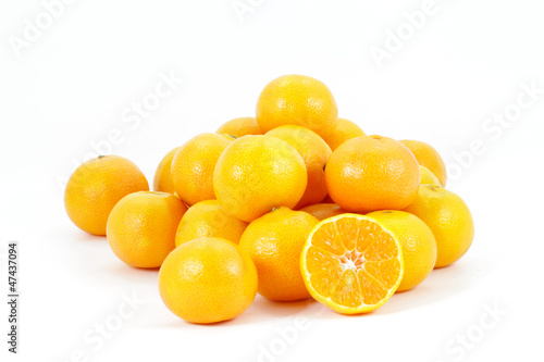 Tangerines heap with one halved showing juicy centre, isolated