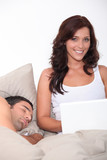 woman having fun on her laptop while her husband is sleeping