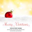 Rote Weihnachtskugel vor weihnachtlichem Hintergrund