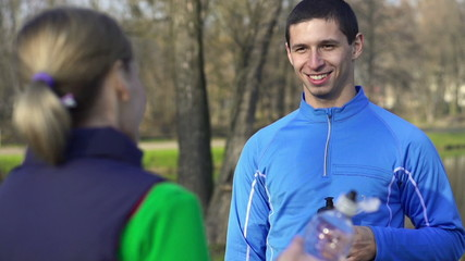 Happy joggers chatting after workout in park, slow motion