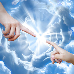 Adult and child hand against each other on the sky