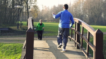 Man and woman jogging in park, super slow motion