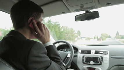 Young handsome man using mobile phone in the car