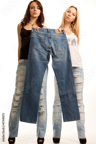 Two girls holding up a pair of jeans