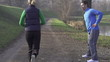 Man stretching, woman jogging in park, crane shot, slow motion