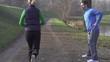 Man stretching, woman jogging in park, crane shot, slow motion