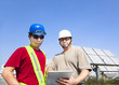 two contractors holding tablet pc and standing before solar pane
