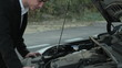 A male looking under the hood of a car