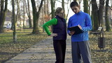Female jogger with personal trainer in park, crane shot