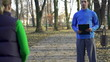 Female jogger with personal trainer in park, super slow motion