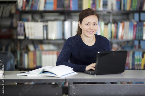 Happy college student working at the library