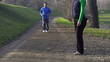 Woman stretching, man jogging in park, crane shot, slow motion