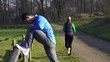 Man stretching, woman jogging in park, crane shot