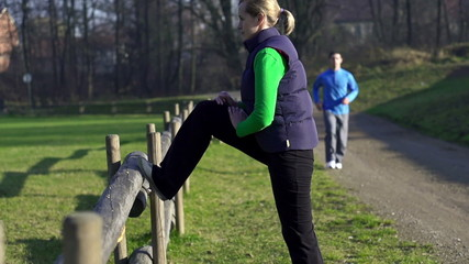Woman stretching, man jogging in park, slow motion,
