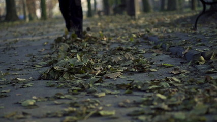 Jogger legs running through leaves, super slow motion