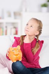 kind mit sparschwein denkt nach
