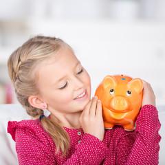 lachendes kind mit sparschwein auf der schulter