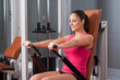 Beautiful smiling girl exercising arms on device
