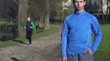 Portrait of young jogger in park, super slow motion