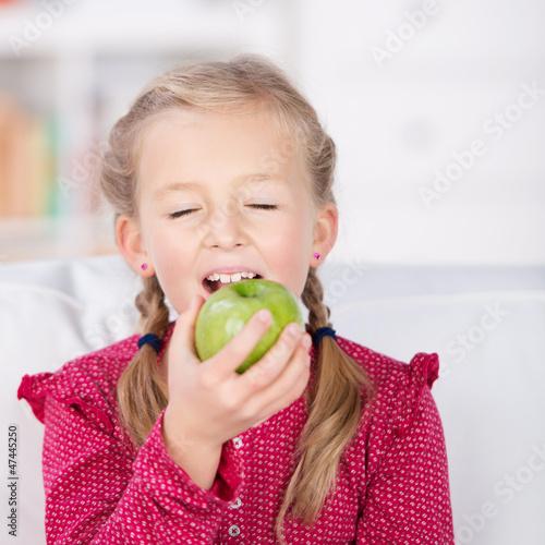 mädchen beißt in grünen apfel