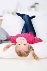 mädchen liegt kopfüber auf dem sofa