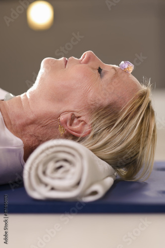Senior woman relaxing and doing therapy with crystals