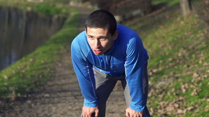 Tired man catching breath during jogging