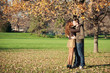 Romantic young couple kissing outdoors in autumn park.