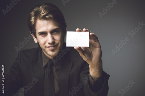 Young man presenting a businesss card