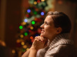Dreaming young woman sitting chair in front of Christmas tree