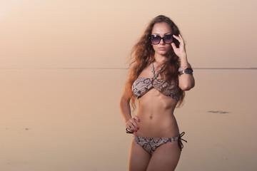 Sexy beautiful woman in bikini on the beach at sunset