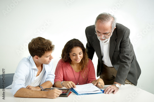 Teacher giving instructions to a couple of students