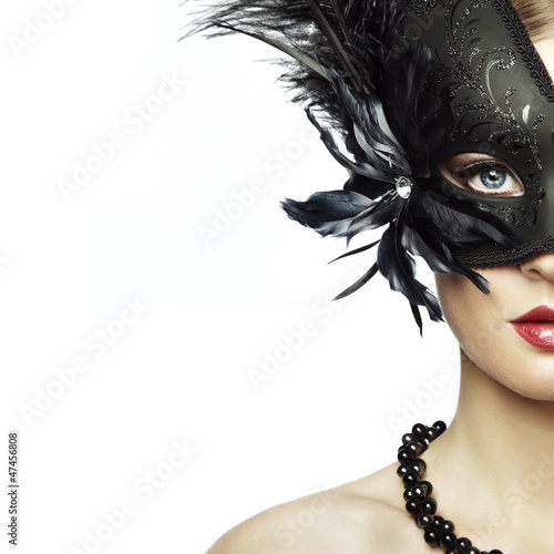 Beautiful young woman in black mysterious venetian mask